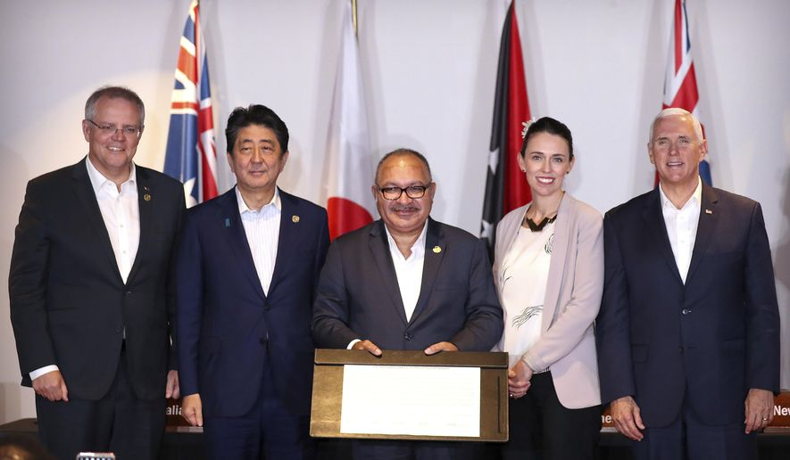 From left, Australian Prime Minister Scott Morrison, Japanese Prime Minister Shinzo Abe, Papua New Guinea's Prime Minister Peter O'Neill, New Zealand's Prime Minister Jacinda Ardern and U.S. Vice President Mike Pence pose for a group photo after signing the Papua New Guinea Electrification Partnership at APEC Haus in Port Moresby, Papua New Guinea, Sunday, Nov. 18, 2018. (AP Photo/Mark Schiefelbein)