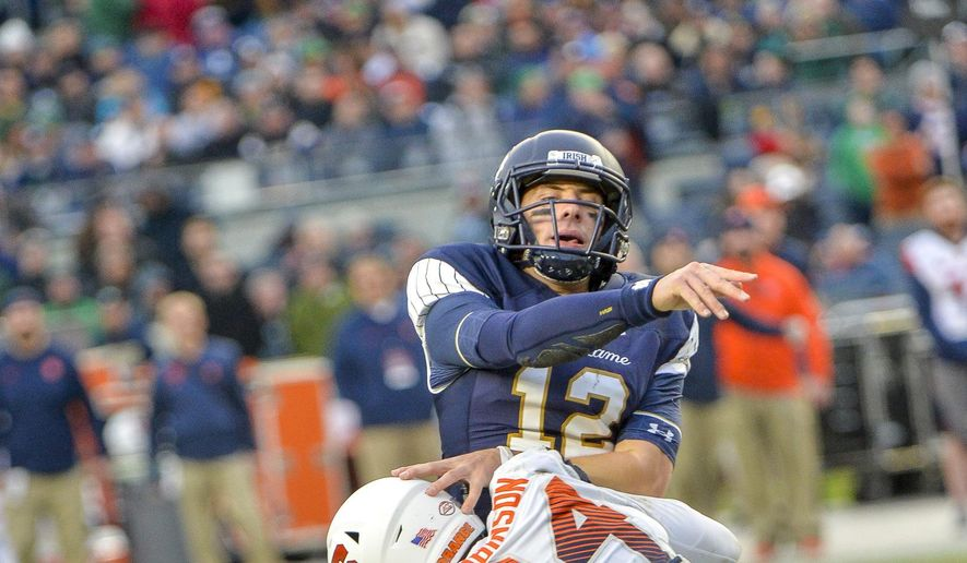 Notre Dame quarterback Ian Book (12) makes throw under pressure from Syracuse defensive lineman Alton Robinson (94) during the first half of an NCAA college football game, Saturday, Nov. 17, 2018, at Yankee Stadium in New York. (AP Photo/Howard Simmons)