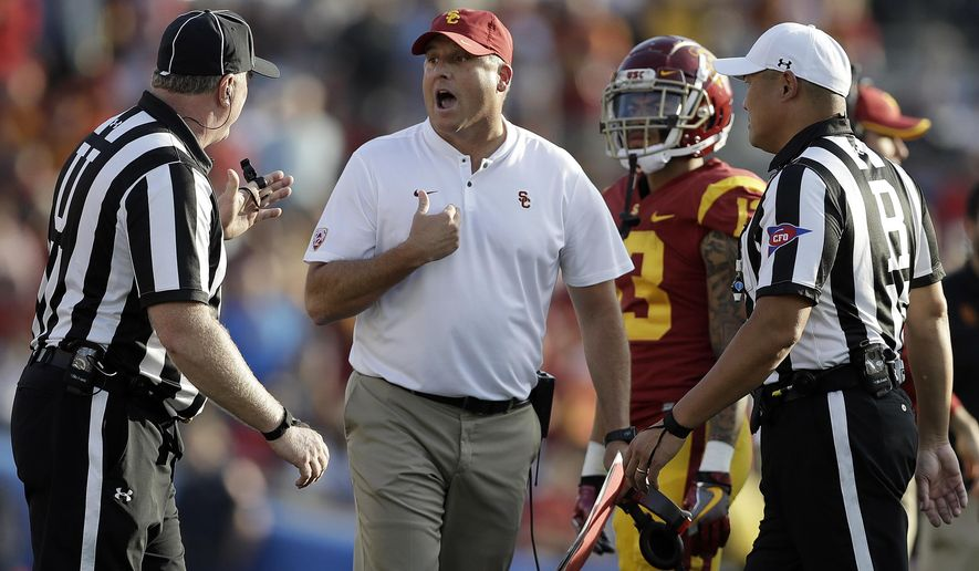 Southern California head coach Clay Helton, center, argues a call with a referee during the second half of an NCAA college football game against UCLA, Saturday, Nov. 17, 2018, in Pasadena, Calif. (AP Photo/Marcio Jose Sanchez)