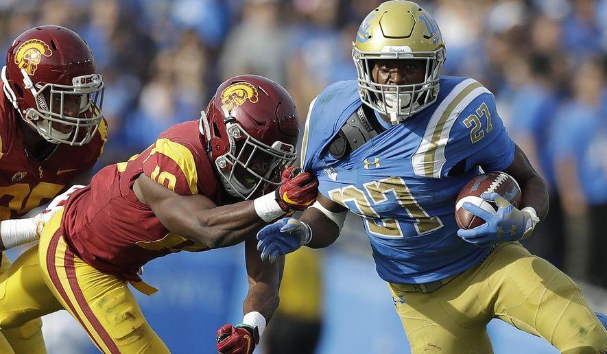 UCLA running back Joshua Kelley (27) rushes as Southern California linebacker John Houston Jr. (10) tugs on his jersey during the first half of an NCAA college football game Saturday, Nov. 17, 2018, in Pasadena, Calif. (AP Photo/Marcio Jose Sanchez)