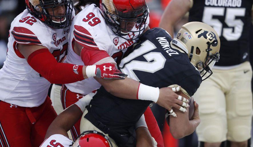 Colorado quarterback Steven Montez (12) is sacked by Utah defensive tackle John Penisini (99), and defensive end Maxs Tupai (92) and defensive tackle Leki Fotu (52) in the second half of an NCAA college football game Saturday, Nov. 17, 2018, in Boulder, Colo. Montez injured his leg on the play. Utah won 30-7. (AP Photo/David Zalubowski)