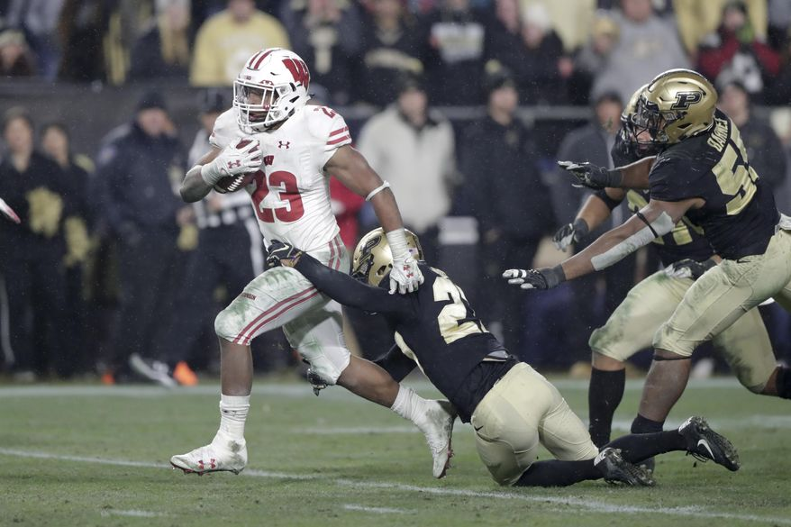 Wisconsin running back Jonathan Taylor (23) breaks the tackle of Purdue safety Navon Mosley (27) on his way to scoring a game-winning touchdown during overtime of an NCAA college football game in West Lafayette, Ind., Saturday, Nov. 17, 2018. Wisconsin defeated Purdue 47-44 in overtime. (AP Photo/Michael Conroy)