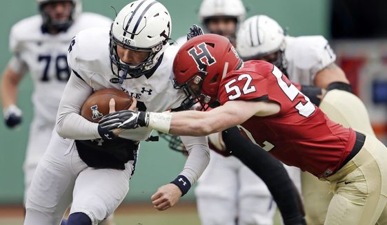 Yale quarterback Griffin O'Connor, left, tries to elude Harvard linebacker Cameron Kline (52) while scrambling for a gain during the first half of an NCAA college football game at Fenway Park in Boston, Saturday, Nov. 17, 2018. (AP Photo/Charles Krupa) ** FILE **