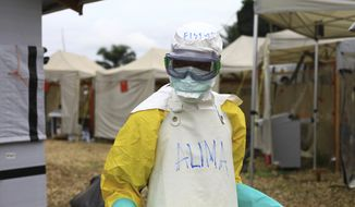 In this photo taken Sunday, Sept 9, 2018, a health worker in protective gear works at an Ebola treatment centre in Beni, Eastern Congo. The current Ebola outbreak in northeastern Congo has become a testing ground with one aid group for the first time treating confirmed Ebola victims in individual biosecure units used in emergencies involving highly infectious diseases. (AP Photo/Al-hadji Kudra Maliro)