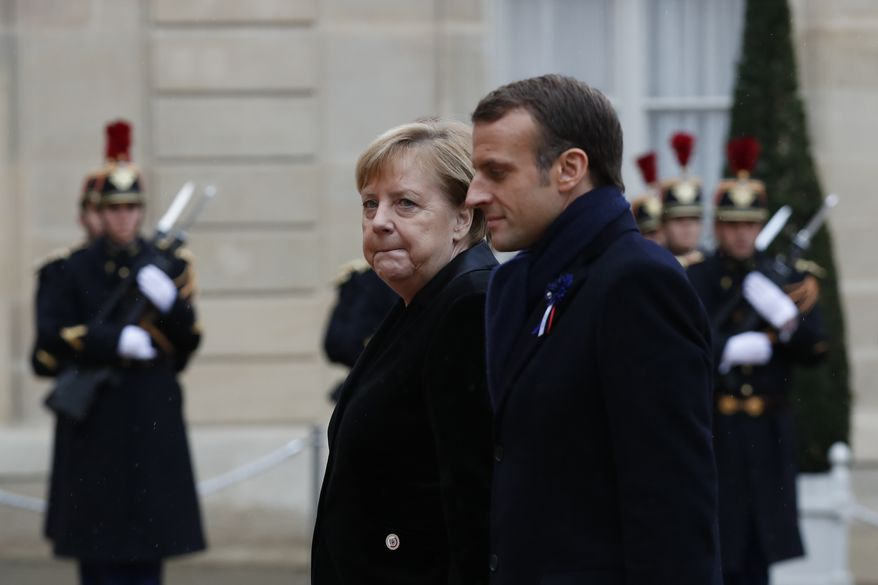 French President Emmanuel Macron and German Chancellor Angela Merkel arrive for a lunch the Elysee Palace after ceremonies Sunday, Nov. 11, 2018 in Paris. International leaders attended a ceremony in Paris on Sunday at mark the 100th anniversary of the end of World War I. (AP Photo/Thibault Camus)
