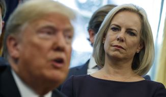 "Secretary of Homeland Security Kirstjen Nielsen looks on as President Donald Trump speaks during a signing ceremony of the ""Cybersecurity and Infrastructure Security Agency Act,"" in the Oval Office of the White House, Friday, Nov. 16, 2018, in Washington. (AP Photo/Evan Vucci)"