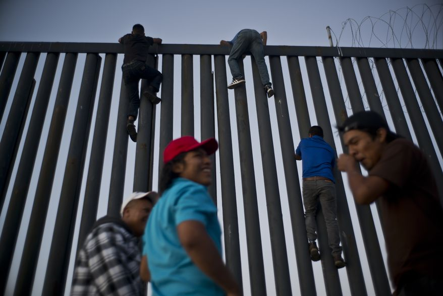 Mexican citizens climb the border fence to take pictures of themselves on top, in Tijuana, Mexico, Sunday, Nov. 18, 2018. While many in Tijuana are sympathetic to the plight of Central American migrants and trying to assist, some locals have shouted insults, hurled rocks and even thrown punches at the migrants. (AP Photo/Ramon Espinosa)