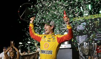 Joey Logano holds his steering wheel after winning the NASCAR Cup Series Championship auto race at the Homestead-Miami Speedway, Sunday, Nov. 18, 2018, in Homestead, Fla. (AP Photo/Terry Renna)