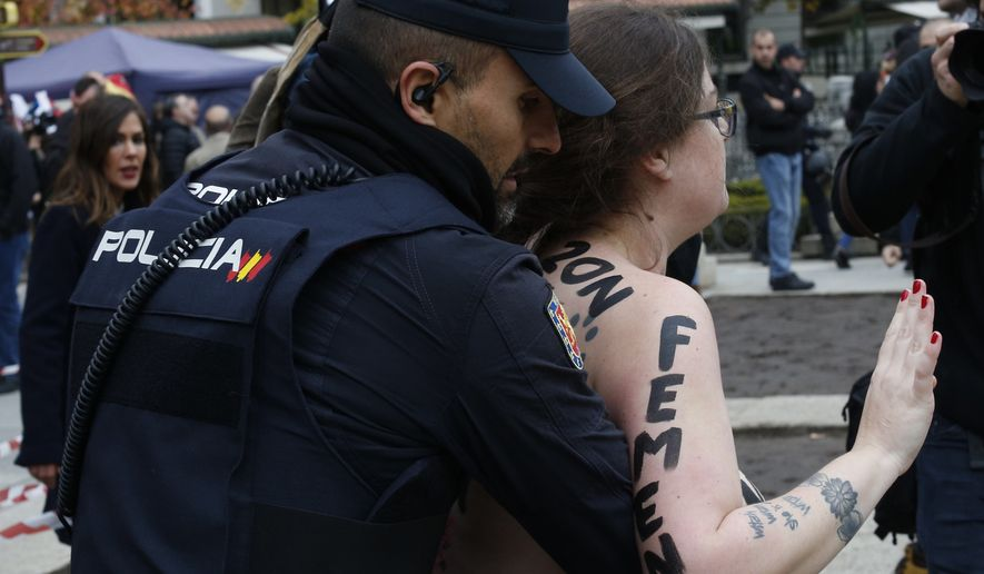 A member of feminist movement Femen is detained by Spanish police after a protest against a far-right rally in Madrid, Spain, Sunday, Nov. 18, 2018. Hundreds of people nostalgic for Spain's fascist past held a peaceful rally on Sunday to mark the 43rd anniversary of dictator Francisco Franco's death. (AP Photo/Manu Fernandez)