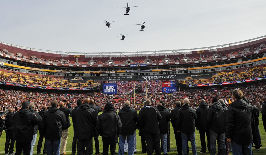 Military helicopters fly over FedEx Field before an NFL football game between the Houston Texans and the Washington Redskins, Sunday, Nov. 18, 2018 in Landover, Md. (AP Photo/Mark Tenally)