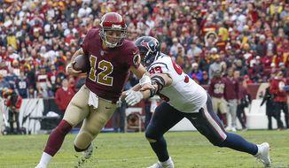 Washington Redskins quarterback Colt McCoy (12) scrambles past Houston Texans defensive end J.J. Watt (99) during the second half of an NFL football game, Sunday, Nov. 18, 2018 in Landover, Md. (AP Photo/Alex Brandon)