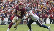 Washington Redskins quarterback Colt McCoy (12) scrambles past Houston Texans defensive end J.J. Watt (99) during the second half of an NFL football game, Sunday, Nov. 18, 2018 in Landover, Md. (AP Photo/Alex Brandon)