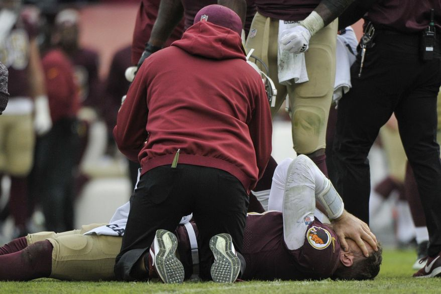 Washington Redskins quarterback Alex Smith, bottom, reacts after an injury during the second half of an NFL football game against the Houston Texans, Sunday, Nov. 18, 2018, in Landover, Md. (AP Photo/Mark Tenally)