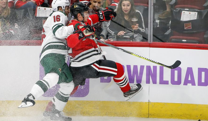 Minnesota Wild left wing Jason Zucker, left, battles for the puck with Chicago Blackhawks defenseman Gustav Forsling, right, during the second period of an NHL hockey game Sunday, Nov. 18, 2018, in Chicago. (AP Photo/Kamil Krzaczynski)