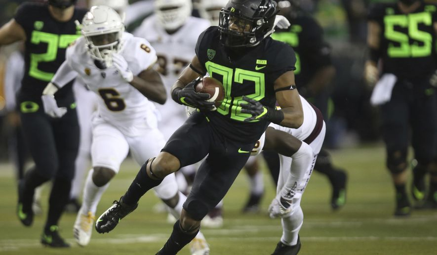 Oregon's CJ Verdell, center, breaks through the Arizona State defense during the second quarter of an NCAA college football game Saturday, Nov. 17, 2018, in Eugene, Ore. (AP Photo/Chris Pietsch)