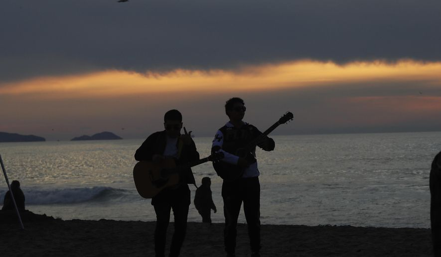 """Musicians are silhouetted against Playa Tijuana, Mexico, Saturday, Nov. 17, 2018. Many of the nearly 3,000 migrants have reached the border with California. The mayor has called the migrants' arrival an """"avalanche"""" that the city is ill-prepared to handle. (AP Photo/Marco Ugarte)"""