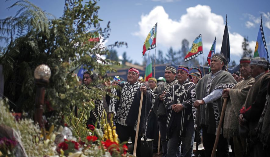 Family and friends Camilo Catrillanca, a Mapuche indigenous youth who was shot in the head when police were chasing unidentified car thieves, hold an ancestral Mapuche rites ceremony next to his coffin in Temuco, Chile, Saturday, Nov. 17, 2018. Indigenous representatives and leaders across the country attended the ceremony. (AP Photo/Luis Hidalgo)