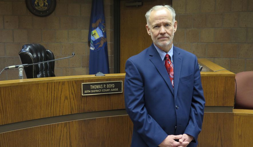 In this Wednesday, Nov. 14, 2018, photo, Ingham County District Court Judge Thomas Boyd poses for a photo in his courtroom in Mason, Mich. Boyd says it's a conflict for judges to order a criminal defendant to pay for the operations of a local court. The Michigan Supreme Court is hearing arguments Monday, Nov. 19 in a case that will determine if it's an illegal tax. (AP Photo/David Eggert)