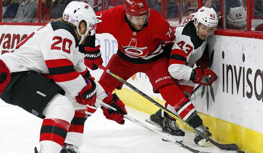 Carolina Hurricanes' Jaccob Slavin (74) battles between New Jersey Devils' Blake Coleman (20) and Brett Seney (43) during the first period of an NHL hockey game, Sunday, Nov. 18, 2018, in Raleigh, N.C. (AP Photo/Karl B DeBlaker)