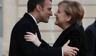 FILE - In this Nov. 11, 2018 file photo, French President Emmanuel Macron hugs German Chancellor Angela Merkel in the courtyard of the Elysee Palace in Paris while marking the 100th anniversary of the end of World War I. Macron and Merkel, both limping in the polls, are looking for common approaches to U.S. President Donald Trump and fixing the flaws in the euro currency. Macron will address the German parliament on Sunday, Nov. 18, 2018. (AP Photo/Thibault Camus, File)