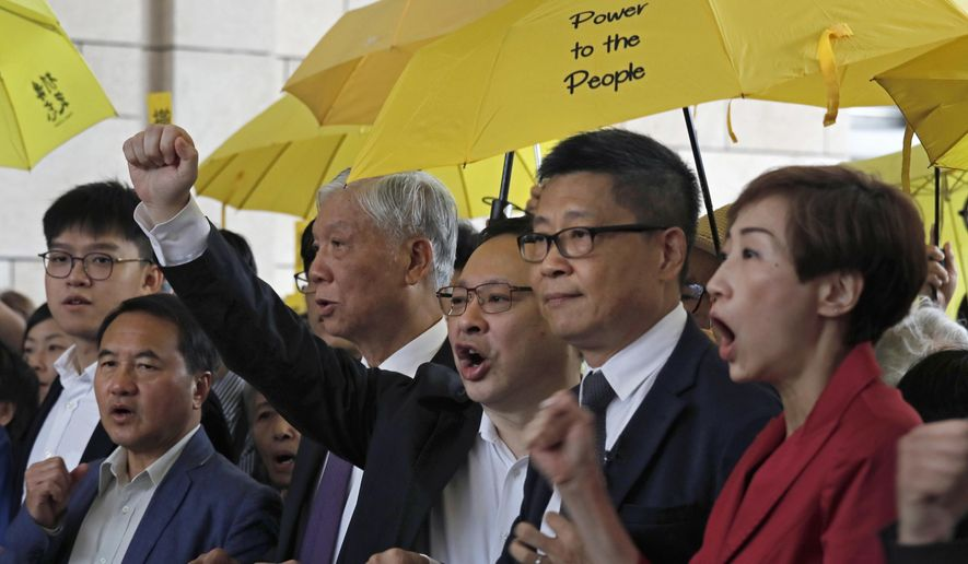 "Occupy Central leaders, from right, Tanya Chan, Chan Kin Man, Benny Tai, Chu Yiu Ming and Lee Wing Tat shout slogans before entering a court in Hong Kong, Monday, Nov. 19, 2018. Nine leaders of the 2014 Hong Kong pro-democracy movement stand trial. The co-founders of the ""Occupy Central"" campaign - legal Prof. Benny Tai Yiu-Ting, sociology professor Chan Kin-man and retired pastor Chu Yiu-ming - are facing charges related to the planning and implementation of the campaign which became part of the large-scale pro-democracy Umbrella Movement protests which were carried out 79 days between September and December 2014. (AP Photo/Vincent Yu)"