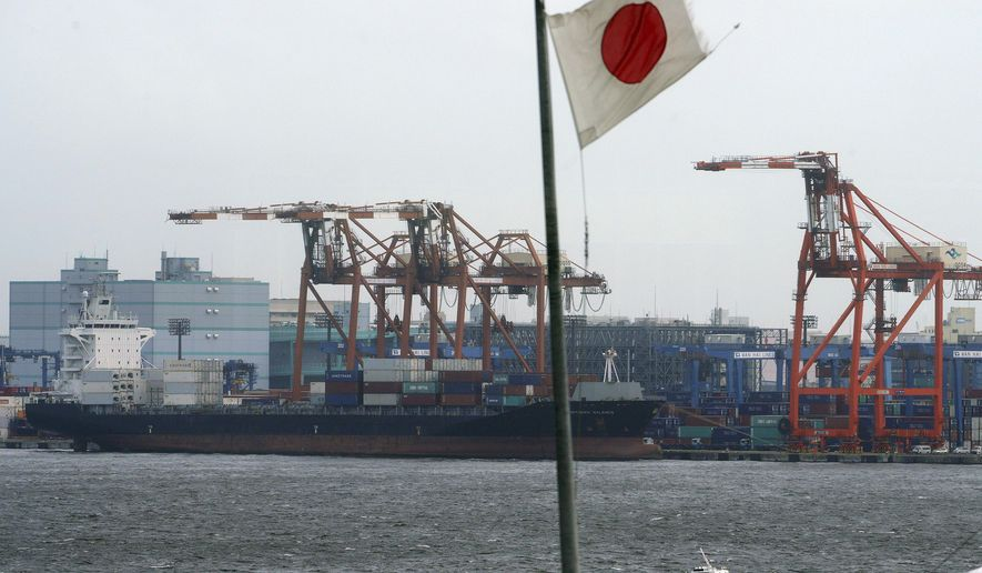 In this Aug. 24, 2018, photo, a Japanese flag is hoisted near the pier of a container terminal in Tokyo. Japan recorded a trade deficit in October but a recovery in exports after getting slammed by natural disasters in September, according to government data released Monday, Nov. 19, 2018. Exports grew 8.2 percent from the same month the previous year, the Finance Ministry said. (AP Photo/Eugene Hoshiko)