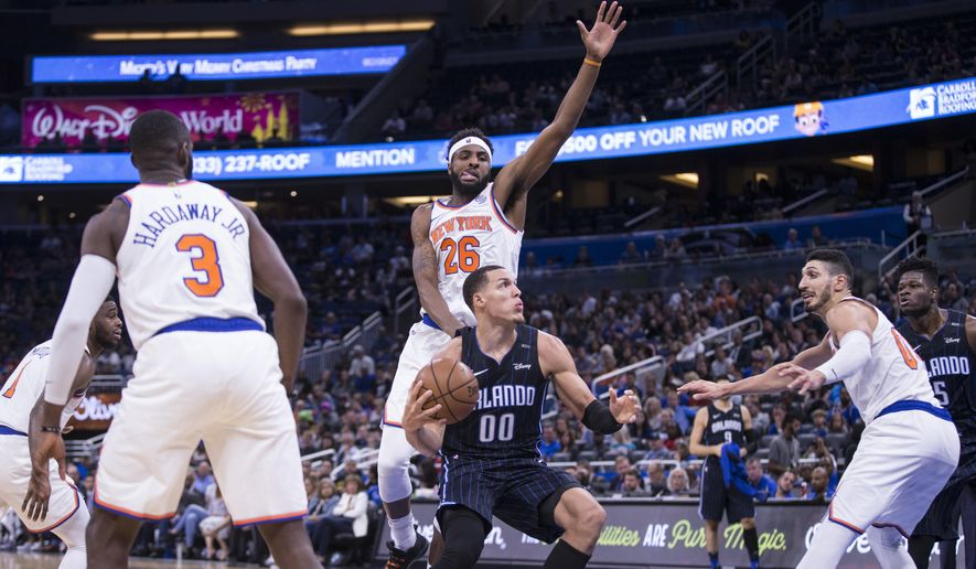 Orlando Magic forward Aaron Gordon (00) goes for a shot while defended by New York Knicks guard Tim Hardaway Jr. (3), center Mitchell Robinson (26) and center Enes Kanter (00) during the first half of an NBA basketball game, Sunday, Nov. 18, 2018, in Orlando, Fla. (AP Photo/Willie J. Allen Jr.)