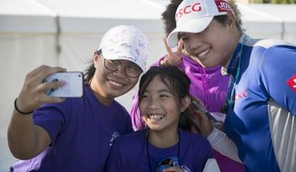 Hazel Paredes, left, and her sister Dylan get a selfie with Ariya Jutanugarn after the third round of the CME Group Tour Championship golf tournament on Saturday, Nov. 17, 2018, at Tiburon Golf Club in Naples Fla. (Amanda Inscore/The News-Press via AP)