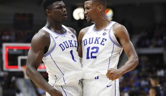 FILE - In this Aug. 15, 2018, file photo, Duke's Zion Williamson, left, and Javin DeLaurier celebrate during the team's exhibition basketball game against Ryerson in Mississauga, Ontario. The Duke juggernaut heads to paradise, where college basketball's most talked-about team will be even more in the spotlight at the Maui Invitational. The top-ranked Blue Devils should be able to handle it. They're 5 for 5 at the Lahaina Civic Center: five trips to Maui, five additions to the already-full trophy case for the trip home. This, of course, is a new team with new stars like Barrett and Williamson, but these freshmen have embraced the spotlight's glare so far and there's little reason to believe it will be any different in Maui. (Mark Blinch/The Canadian Press via AP, File)