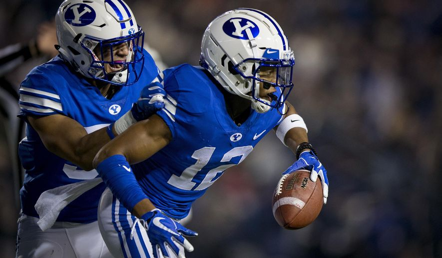 BYU linebacker Isaiah Kaufusi (53) and defensive back Malik Moore (12) celebrate Moore's interception against New Mexico State during an NCAA college football game Saturday, Nov. 17, 2018, in Provo, Utah. (Isaac Hale/Daily Herald via AP)