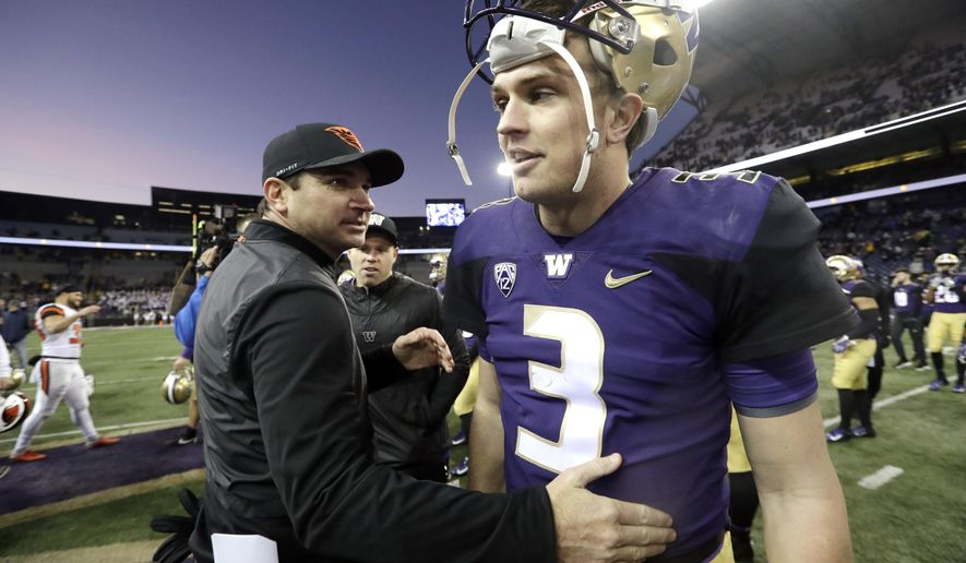 Oregon State head coach Jonathan Smith, left, greets Washington quarterback Jake Browning after an NCAA college football game Saturday, Nov. 17, 2018, in Seattle. (AP Photo/Elaine Thompson)