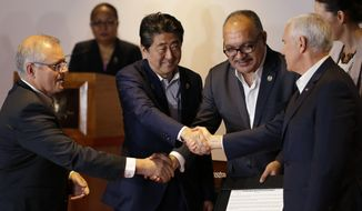 From left, Australian Prime Minister Scott Morrison, Japan Prime Minister Shinzo Abe, Papua New Guinea Prime Minister Peter O'Neill and U.S. Vice President Mike Pence shake hands during the Leaders Electrification Project meeting as part of the APEC 2018 at Port Moresby, Papua New Guinea on Sunday, Nov. 18, 2018. In a statement issued to media, Papua New Guinea has invited Australia, Japan, New Zealand and the United States to work together to support its enhanced connectivity and the goal of connecting 70% of its population to electricity by 2030. Currently only about 13% of Papua New Guinea's population have reliable access to electricity. (AP Photo/Aaron Favila)