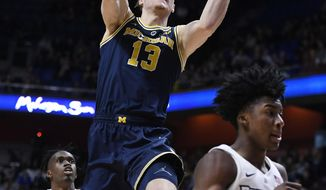 Michigan's Ignas Brazdeikis (13) goes up to the basket between Providence's Jimmy Nichols Jr. (5) and David Duke (3) during the first half of an NCAA college basketball game, Sunday, Nov. 18, 2018, in Uncasville, Conn. (AP Photo/Jessica Hill)