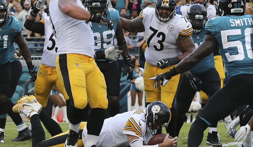 Pittsburgh Steelers quarterback Ben Roethlisberger dives over the goal line for the go ahead touchdown in front of Jacksonville Jaguars outside linebacker Telvin Smith, right, during the final seconds of an NFL football game, Sunday, Nov. 18, 2018, in Jacksonville, Fla. (AP Photo/Gary McCullough)