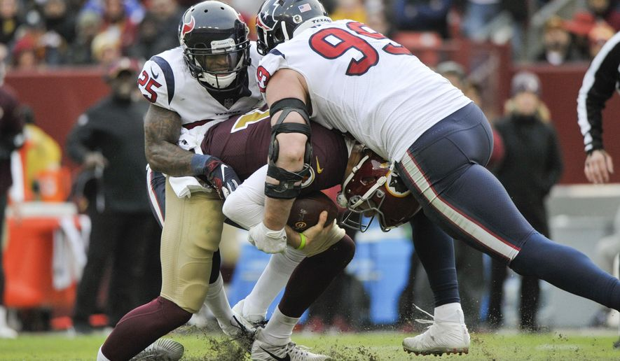 Washington Redskins quarterback Alex Smith (11) ankle is injured as he is sacked by Houston Texans defensive end J.J. Watt (99) and Houston Texans strong safety Kareem Jackson (25) during the second half of an NFL football game, Sunday, Nov. 18, 2018 in Landover, Md. (AP Photo/Mark Tenally)