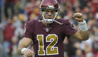 Washington Redskins quarterback Colt McCoy (12) celebrates running back Adrian Peterson's touchdown during the second half of an NFL football game against the Houston Texans, Sunday, Nov. 18, 2018 in Landover, Md. (AP Photo/Mark Tenally)