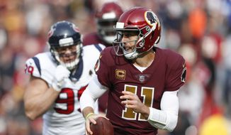Washington Redskins quarterback Alex Smith (11) scrambles past Houston Texans defensive end J.J. Watt (99) during the first half of an NFL football game, Sunday, Nov. 18, 2018, in Landover, Md. (AP Photo/Pablo Martinez Monsivais) **FILE**