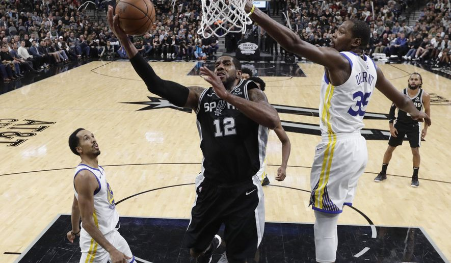 San Antonio Spurs forward LaMarcus Aldridge (12) scores past Golden State Warriors forward Kevin Durant (35) during the second half of an NBA basketball game, Sunday, Nov. 18, 2018, in San Antonio. San Antonio won 104-92. (AP Photo/Eric Gay)