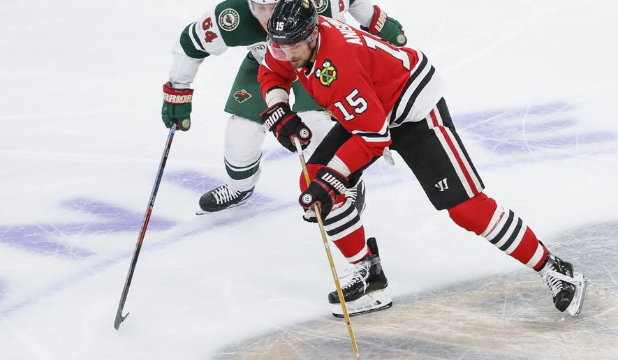 Chicago Blackhawks center Artem Anisimov (15) battles for the puck with Minnesota Wild right wing Mikael Granlund (64) during the third period of an NHL hockey game Sunday, Nov. 18, 2018, in Chicago. (AP Photo/Kamil Krzaczynski)