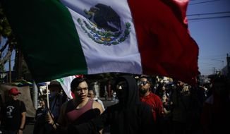 "A demonstrator carries a Mexican flag during a protest against the presence of thousands of Central American migrants in Tijuana, Mexico, Sunday, Nov. 18, 2018. Protesters accused the migrants of being messy, ungrateful and a danger to Tijuana; complained about how the caravan forced its way into Mexico, calling it an ""invasion,"" and voiced worries that their taxes might be spent to care for the group as they wait possibly months to apply for U.S. asylum. (AP Photo/Ramon Espinosa)"