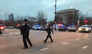 Chicago Police officers walk outside Mercy Hospital on the city's South Side where authorities say a shooting at the hospital has wounded multiple people, including a suspect and a police officer, Monday, Nov. 19, 2018, in Chicago. (AP Photo/Amanda Seitz)