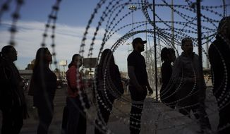Pedestrians stand near barbed wire at a legal Mexico-U.S. border crossing as they prepare to leave Tijuana, Mexico, Monday, Nov. 19, 2018. The United States closed off northbound traffic for several hours at the busiest border crossing with Mexico to install new security barriers on Monday, a day after hundreds of Tijuana residents protested against the presence of thousands of Central American migrants. (AP Photo/Ramon Espinosa)