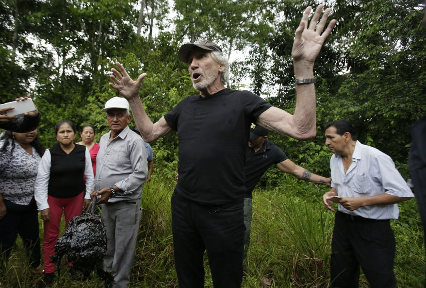 Musician and activist Roger Waters talks as a settler holds a lump of oil polluted dirt, at the Aguarico 4 oil well in the Amazon region of Ecuador, Monday, Nov. 19, 2018. Ecuadoreans tried to get Chevron to pay for environmental damage caused to a rainforest by Texaco during its operation of an oil consortium from 1972 to 1990, and were ultimately successful in Ecuador where a court there ordered Chevron to pay $9.5 billion. But in 2014, a judge in New York invalidated the Ecuador judgment, deeming it was obtained through legal malpractice. (AP Photo/Dolores Ochoa)