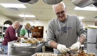 Elks Lodge BPOE 350 member Mark Hannah pulls turkey for the community Thanksgiving meal on Monday, Nov.  19, 2018 in Ashland, Ky. Volunteers and lodge members serve 1,600 free meals to the community. (Kevin Goldy/The Daily Independent via AP)