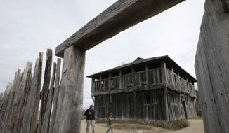 In this Sunday, Nov. 18, 2018, photo, visitors walk past a fort at Plymouth Plantation living history museum village, in Plymouth, Mass., where visitors can get a glimpse into the world of the 1627 Pilgrim village. Plymouth, where the Pilgrims came ashore in 1620, is gearing up for a 400th birthday, and everyone's invited, especially the native people whose ancestors wound up losing their land and their lives. (AP Photo/Steven Senne)