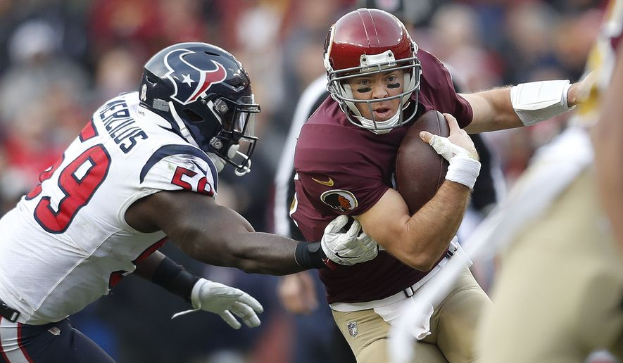 Washington Redskins quarterback Colt McCoy (12) runs with the ball past Houston Texans outside linebacker Whitney Mercilus (59) during the second half of an NFL football game against the Houston Texans, Sunday, Nov. 18, 2018, in Landover, Md.(AP Photo/Pablo Martinez Monsivais)