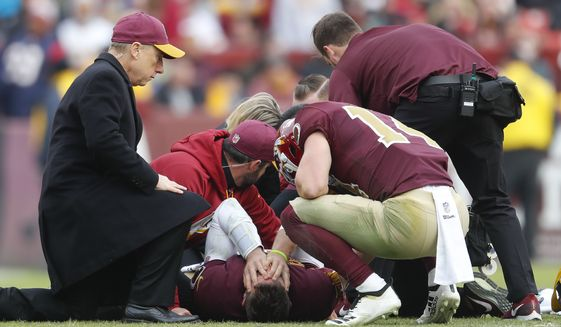 Washington Redskins quarterback Alex Smith (11) holds his head after an injury during the second half of an NFL football game against the Houston Texans, Sunday, Nov. 18, 2018 in Landover, Md. Kneeling down to talk to Smith is teammate Trey Quinn (14). (AP Photo/Pablo Martinez Monsivais) ** FILE **