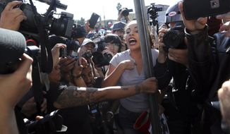 "An anti-migrant demonstrator is surrounded by the press as she argues with a woman during a protest against the presence of thousands of Central American migrants in Tijuana, Mexico, Sunday, Nov. 18, 2018. Protesters accused the migrants of being messy, ungrateful and a danger to Tijuana; complained about how the caravan forced its way into Mexico, calling it an ""invasion,"" and voiced worries that their taxes might be spent to care for the group as they wait possibly months to apply for U.S. asylum. (AP Photo/Rodrigo Abd)"