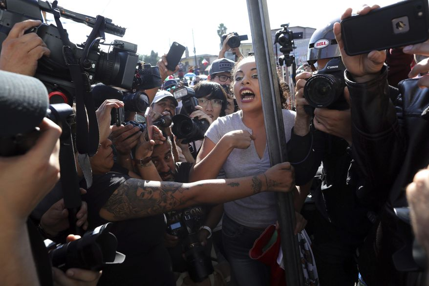 """An anti-migrant demonstrator is surrounded by the press as she argues with a woman during a protest against the presence of thousands of Central American migrants in Tijuana, Mexico, Sunday, Nov. 18, 2018. Protesters accused the migrants of being messy, ungrateful and a danger to Tijuana; complained about how the caravan forced its way into Mexico, calling it an """"invasion,"""" and voiced worries that their taxes might be spent to care for the group as they wait possibly months to apply for U.S. asylum. (AP Photo/Rodrigo Abd)"""