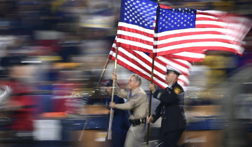 Fire and and law enforcement first responders run with United States flags as they lead players out of the tunnel before an NFL football game between the Los Angeles Rams and the Kansas City Chiefs, Monday, Nov. 19, 2018, in Los Angeles. (AP Photo/Kelvin Kuo)